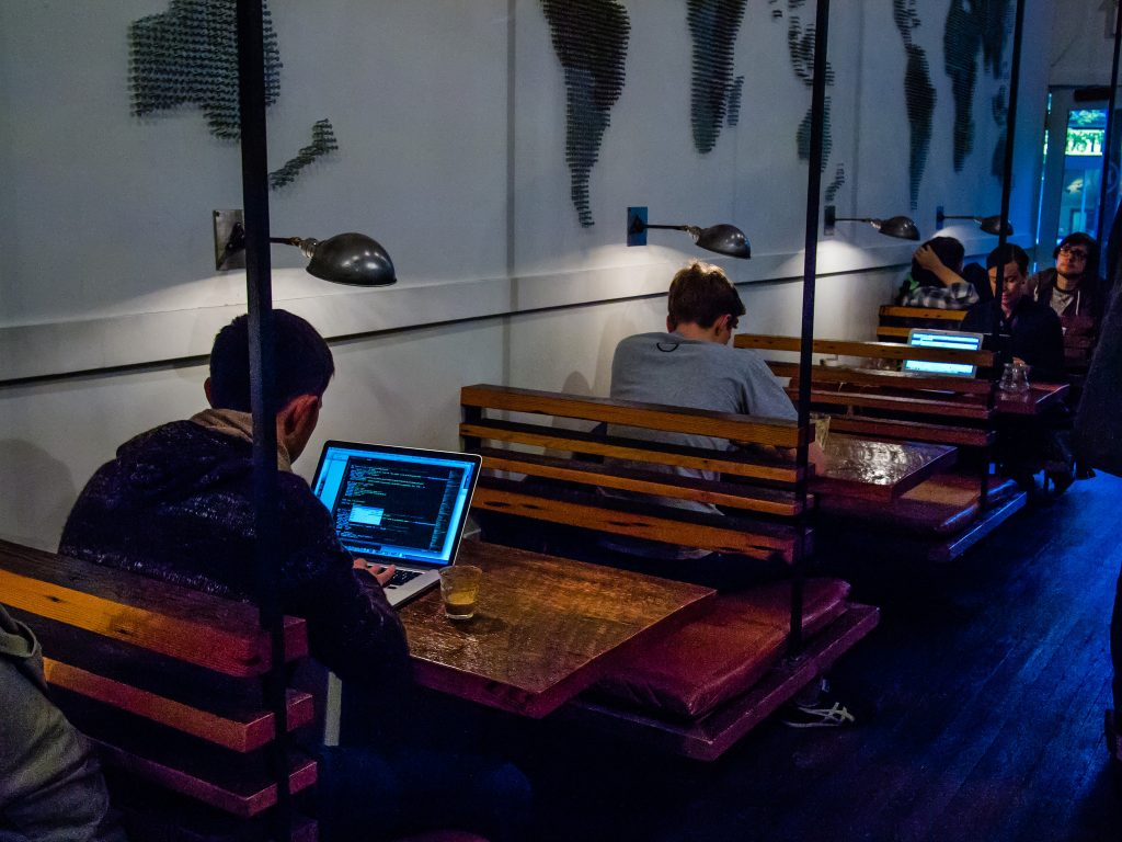 image of a guy at a restaurant coding in a booth on his computer