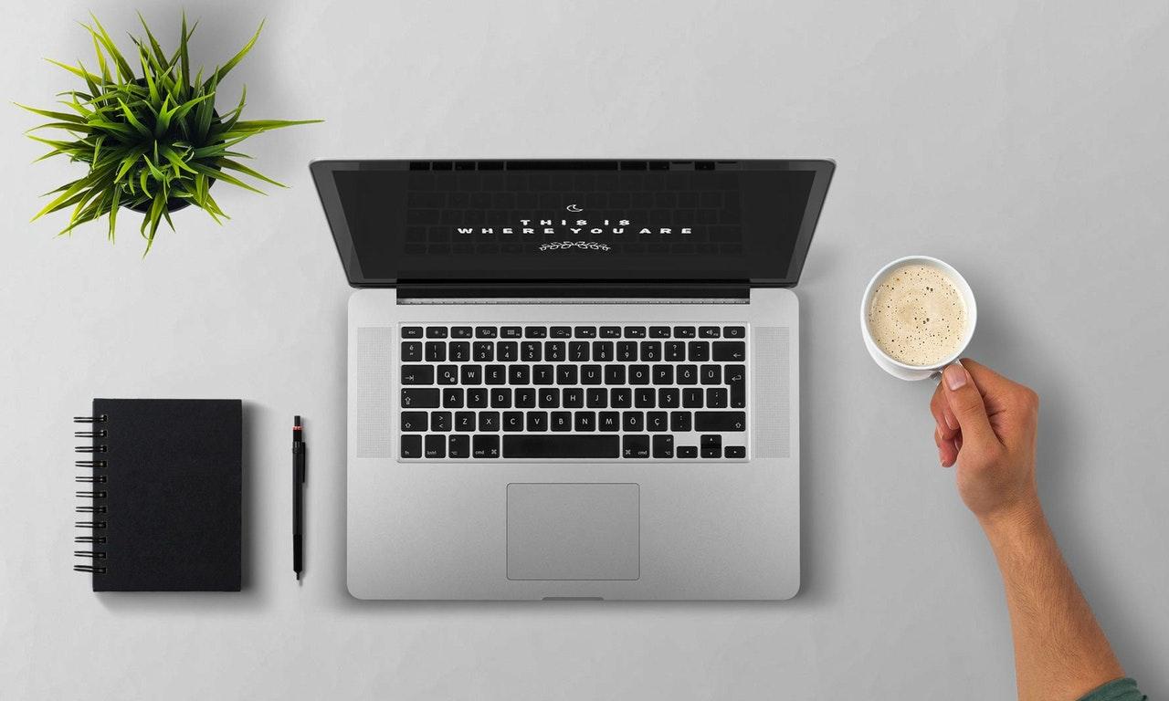 Man using laptop having coffee